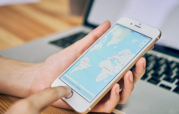 女性は、ショー画面のgoogleマップで電話を保持 Premium写真