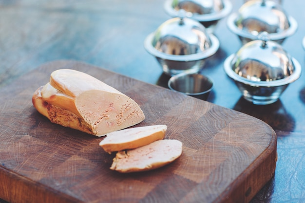 Goose liver on a wooden board in the restaurant before cooking. Premium Photo
