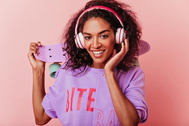 스케이트 보드 미소와 함께 화려한 아프리카 여자입니다. 핑크에 고립 된 헤드폰에 낭만적 인 곱슬 소녀의 실내 초상화. 무료 사진