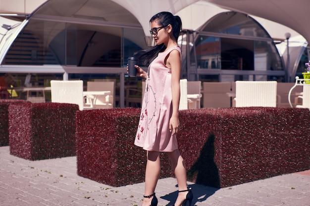 Великолепная азиатская женщина в модном платье на террасе ресторана Бесплатные Фотографии