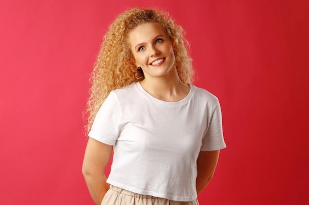 カメラでポーズをとる巻き毛のゴージャスな美しい若い女性のクローズアップ Premium写真