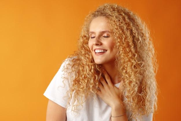 Великолепная красивая молодая женщина с вьющимися волосами позирует перед камерой Premium Фотографии
