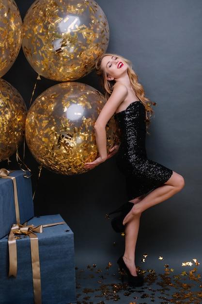 長い巻き毛のブロンドの髪、かかと、前向きな感情を表現する黒い高級ドレスを持つゴージャスな美しい若い女性。誕生日パーティーを祝って、楽しんで、プレゼントして、幸せ。 無料写真