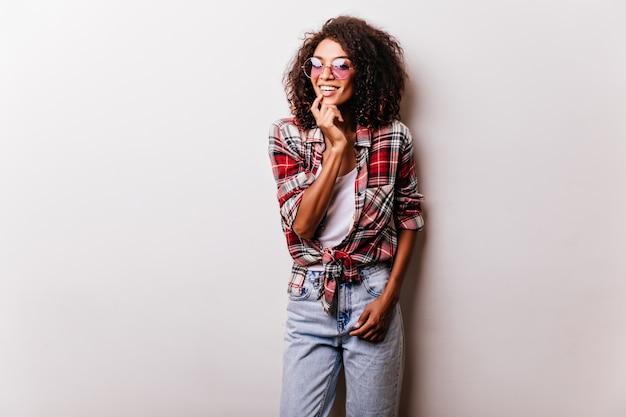 笑顔のヴィンテージジーンズのゴージャスな黒人女性モデル。遊び心のあるアフリカの女性の肖像画は赤い市松模様のシャツを着ています。 無料写真
