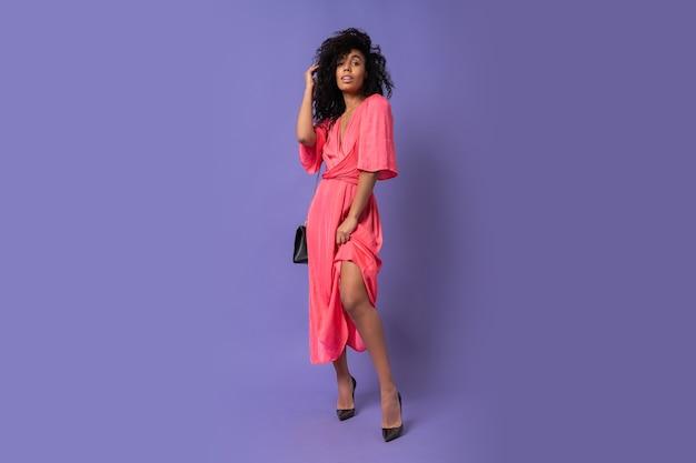 Splendida donna nera in abito da festa rosa in posa sopra la parete viola. indossare i tacchi. intera lunghezza. Foto Gratuite