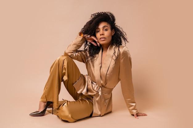 Великолепная темнокожая женщина с красивыми волнистыми волосами в элегантном золотом атласном костюме позирует над бежевой стеной. весенний модный образ. Бесплатные Фотографии