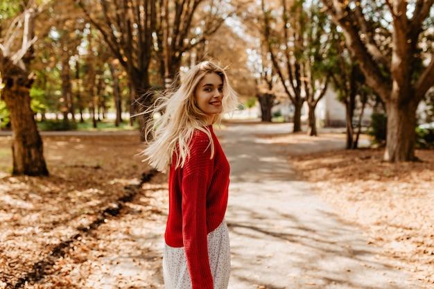 美しい公園で楽しい時間を過ごしているゴージャスなブロンド。黄色の葉の間でふざけて笑っているかわいい女の子。 無料写真