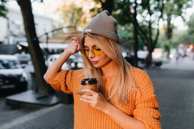 Splendida donna bionda con cappello grigio che cammina a casa dopo l'allenamento in palestra e bere latte Foto Gratuite