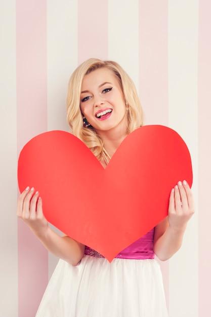 Splendida donna bionda con un grande cuore rosso Foto Gratuite