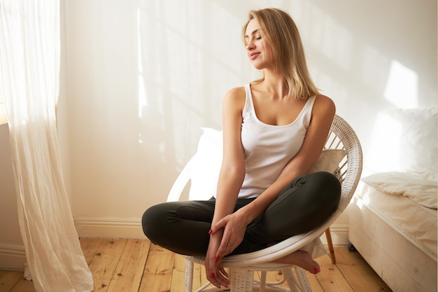 Bellissima giovane donna bionda in abiti casual seduto in poltrona con le gambe piegate, avendo rilassato l'espressione del viso spensierata, guardando attraverso la finestra, godendosi la calda luce del sole, tenendo gli occhi chiusi Foto Gratuite