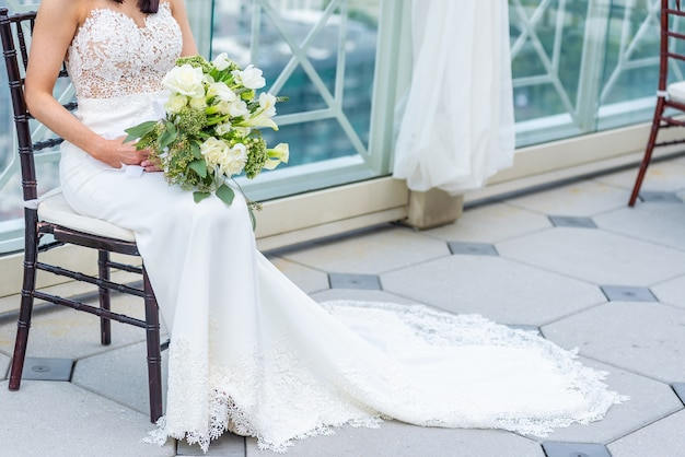 Gorgeous bride with a luxury wedding dress sitting on a chair holding a bridal bouquet Free Photo