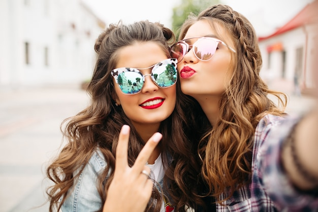 Gorgeous brunette girlfriends with hairstyle, mirrored sunglasses and red lips making selfie with duck face. Premium Photo