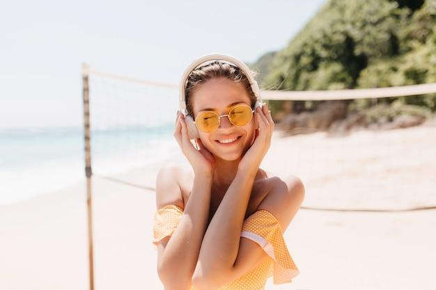 Splendida donna castana che gode della canzone con gli occhi chiusi in spiaggia. colpo esterno di una ragazza accattivante in cuffie bianche agghiacciante in spiaggia selvaggia. Foto Gratuite