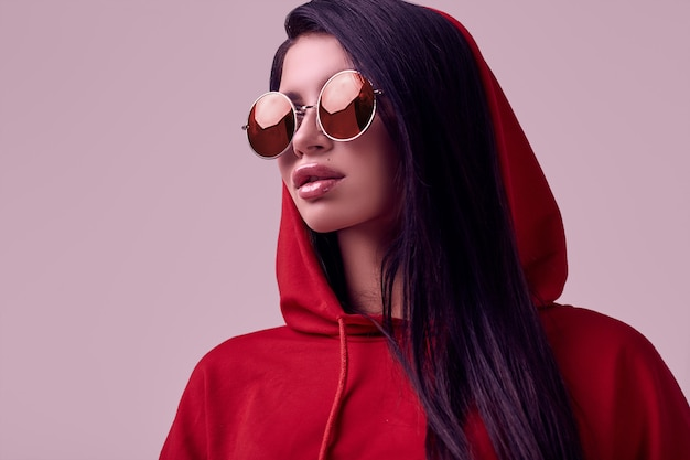 Gorgeous brunette woman in fashion red hoodie in studio Premium Photo