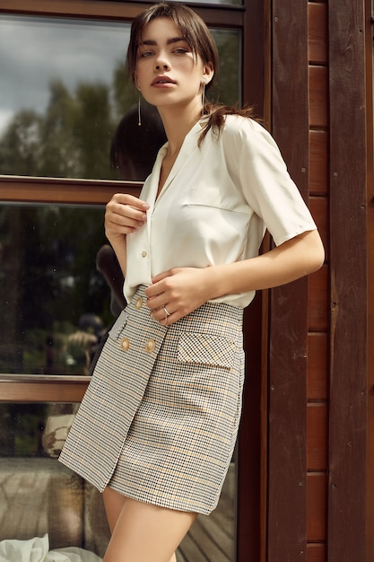 Gorgeous brunette woman in fashion skirt and white blouse Premium Photo