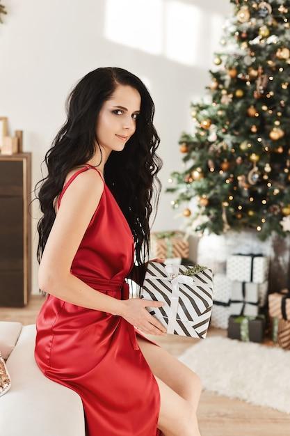 Великолепная брюнетка в красном вечернем платье держит рождественскую подарочную коробку Premium Фотографии