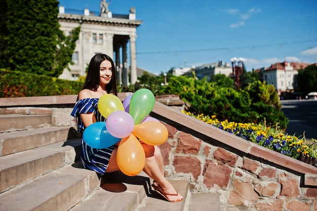 Gorgeous brunette woman at street of city with balloons at hands. Premium Photo