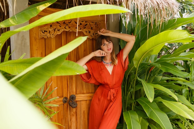 Gorgeous  brunette woman in stylish summer outfit  enjoing vacation in luxury resort. exotic  garden with tropical plants. Free Photo