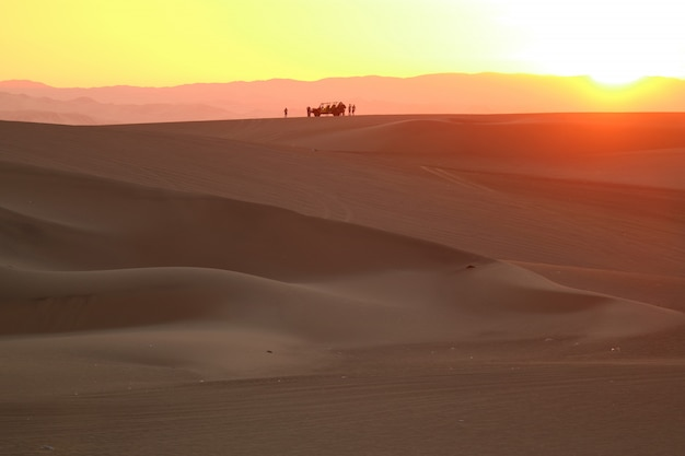 Gorgeous color layer of sunset over the sand dune of huacachina desert with the silhouette of dune baggy and people Premium Photo