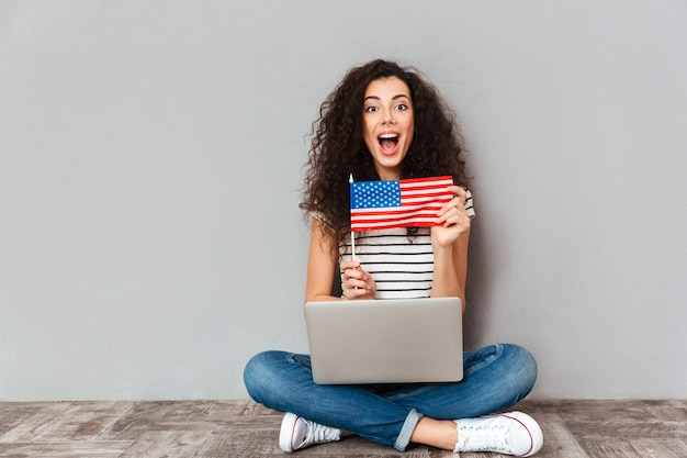 Gorgeous female with beautiful smile sitting in lotus pose with silver computer on legs demonstrating american flag over grey wall Free Photo