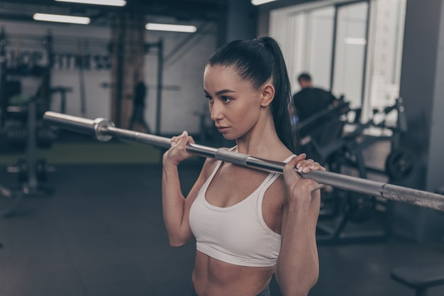 Gorgeous fit and toned sportswoman lifting barbell at the gym, copy space on the side Premium Photo