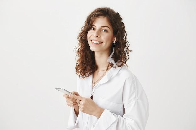Великолепная счастливая женщина с помощью мобильного телефона, прослушивания музыки в беспроводных наушниках Бесплатные Фотографии