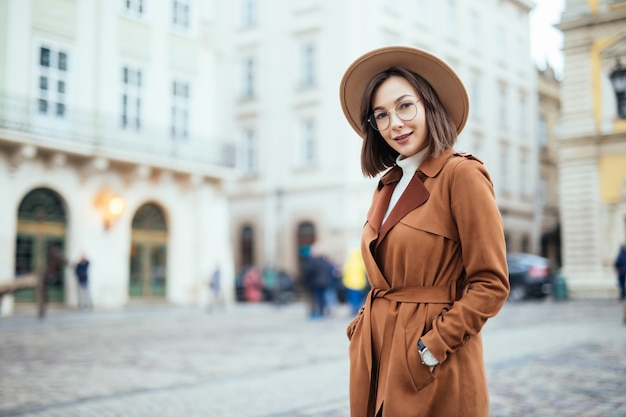 Великолепная в современном коричневом пальто позирует на улице в центре города Бесплатные Фотографии
