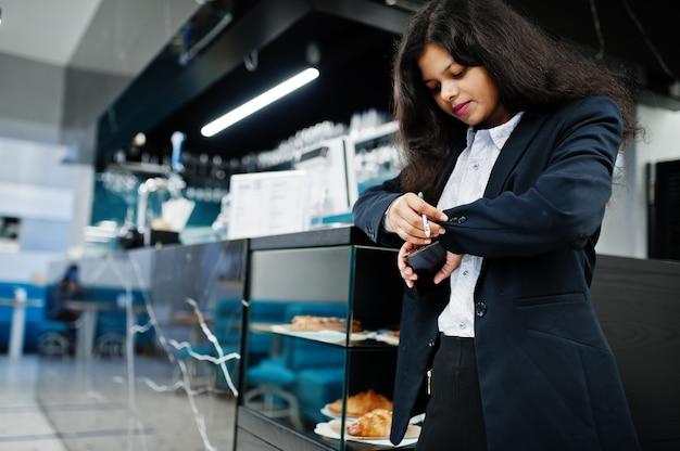 화려한 인도 여자는 바 카운터 근처 카페에서 공식적인 포즈를 취합니다. 프리미엄 사진