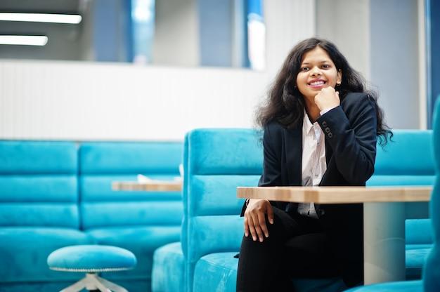 화려한 인도 여자는 카페에서 공식적인 포즈를 입는다. 프리미엄 사진