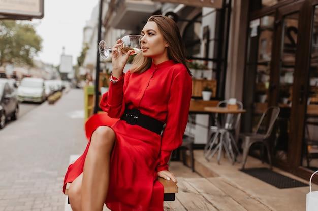 Шикарная дама в дорогом авторском платье пьет изысканное игристое вино из хрусталя. блогер сидит в кафе в полный рост Бесплатные Фотографии