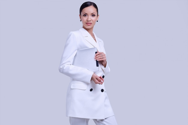 Gorgeous latin women in fashion white suit with digital tablet Premium Photo