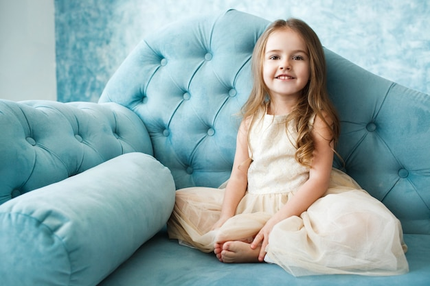 Gorgeous little girl with dark blonde hair lies on blue couch Free Photo