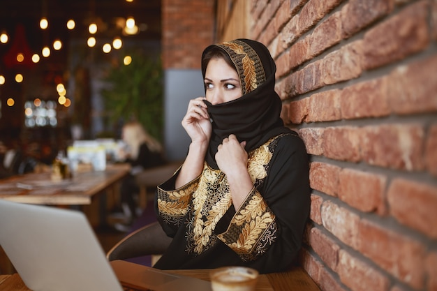 Gorgeous muslim woman covering her face with scarf while sitting at coffee shop. on desk are laptop and coffee. Premium Photo