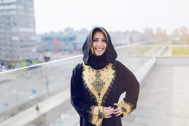 Gorgeous muslim woman in traditional wear looking at camera and posing while standing on rooftop. Premium Photo