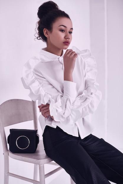 白で隔離のファッショナブルなビジネススーツの巻き毛を持つエレガントな黒人女性のゴージャスな肖像画 無料写真