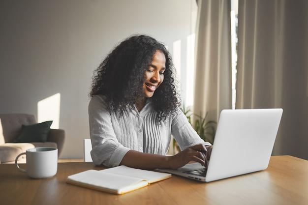 ゴージャスなポジティブな若い暗い肌の女性ブロガーが一般的なラップトップでキーボード操作し、笑顔で、旅行ブログの新しいコンテンツを作成しながらインスピレーションを得て、日記とマグカップを持って机に座っています 無料写真