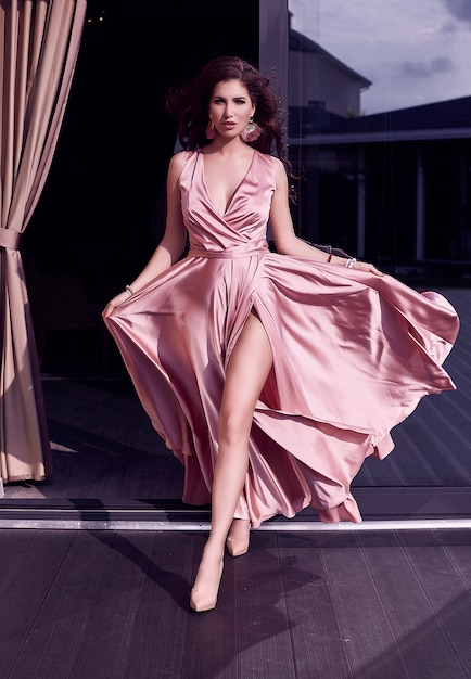 Gorgeous sensual brunette model in fashion pink dress on terrace Premium Photo
