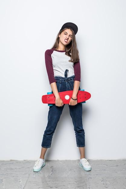 Великолепная фигуристка, держащая в руках красный скейтборд, изолирована на белой стене Бесплатные Фотографии