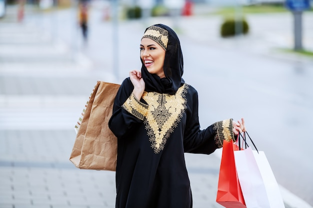 Gorgeous smiling positive arab woman in traditional wear holding shopping bags in hand walking on the street and feeling satisfied with her shopping. Premium Photo