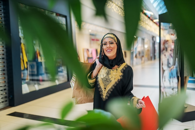 Gorgeous smiling young arab woman in traditional wear standing in shopping mall with shopping bags in hands Premium Photo