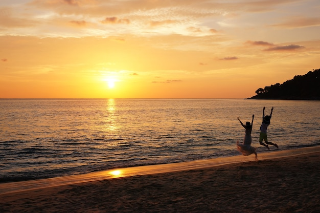 Gorgeous sunset with a jumping couple. Premium Photo