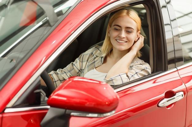 ゴージャスな女性が彼女の車に座って、サイドミラーで見ている彼女の髪を修正します。 Premium写真