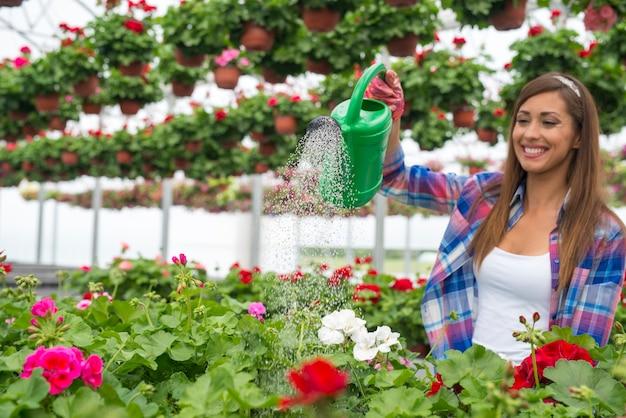 温室フラワーセンターの植物に水をまく彼女の顔に歯を見せる笑顔を持つゴージャスな女性の花屋 無料写真