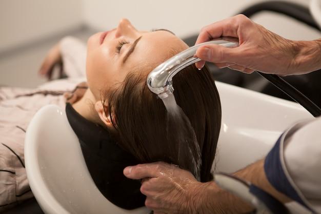 Шикарная женщина моет волосы парикмахером Premium Фотографии