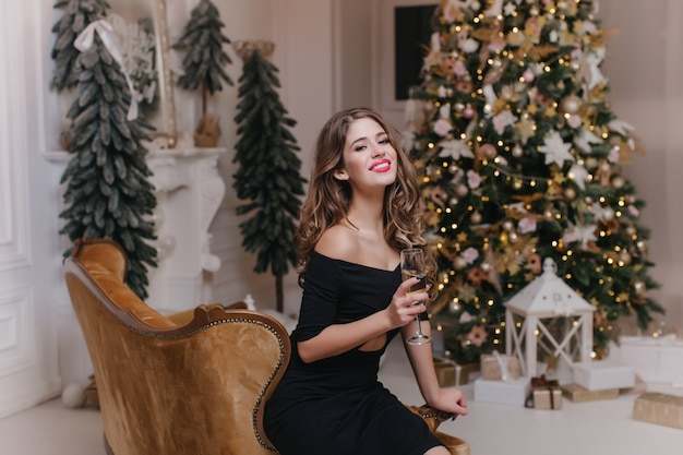 Великолепная женщина в черном наряде сидит на коричневом диване с бокалом вина. портрет уверенно длинноволосой девушки, празднующей зимние каникулы с елкой на стене. Бесплатные Фотографии