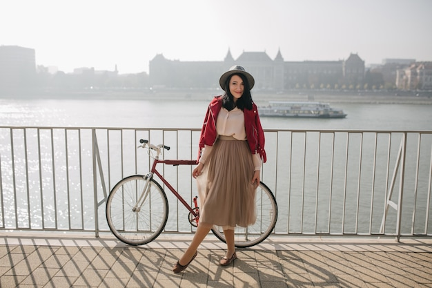 川の近くで喜んでポーズをとる古着のゴージャスな女性 無料写真