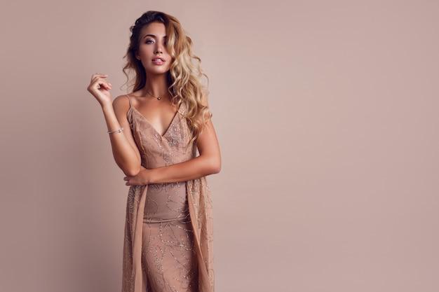 Gorgeous woman with blonde wavy hair wearing elegant beige dress Free Photo