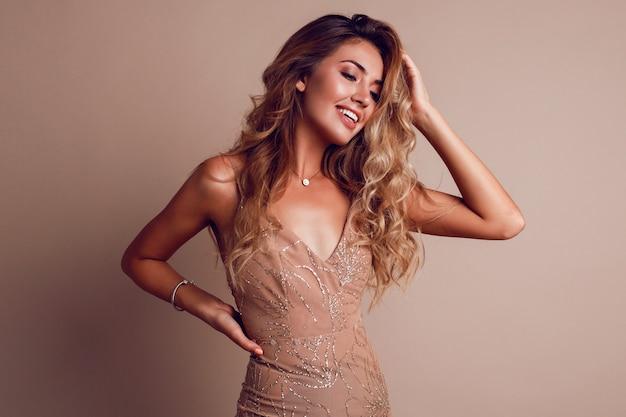 Великолепная женщина со светлыми волнистыми волосами в элегантном бежевом платье Бесплатные Фотографии
