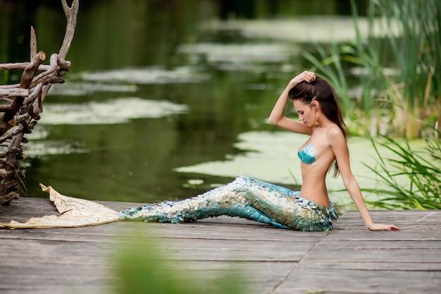 La donna splendida con i capelli lunghi e vestita come una sirena si siede sul ponte sull'acqua Foto Gratuite