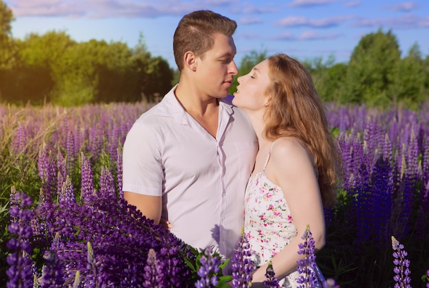 Premium Photo A Gorgeous Young Couple In Love Kissing In A Field Of Flowers